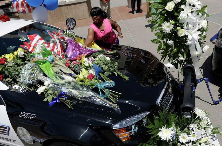 Cynthia Ware places flowers on a make-shift memorial at the Dallas police headquarters. Photo: Eric Gay, STF / Copyright 2016 The Associated Press. All rights reserved. This material may not be published, broadcast, rewritten or redistribu