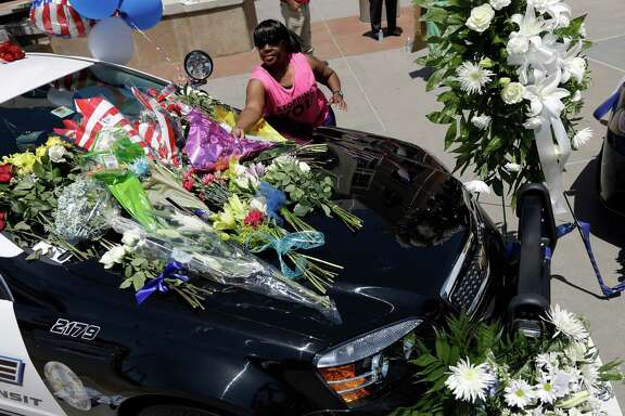 Cynthia Ware places flowers on a make-shift memorial at the Dallas police headquarters.