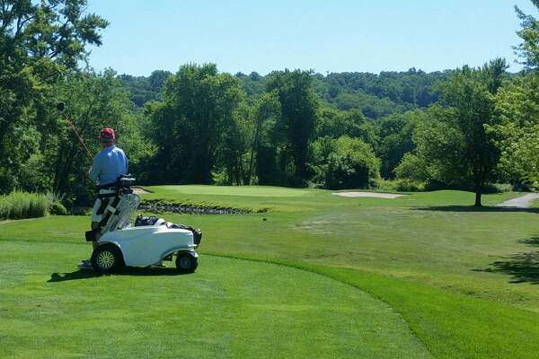 "A golfer on the fourth hole of Candlewood Valley Golf Club in New Milford, Conn. swings while using a ""para-cart."""
