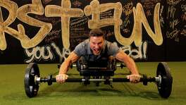 Clark Bartram demonstrates the Frog Fitness machine, invented by Richard Pearce, Wednesday, July 20, 2016, in The Woodlands. Frog Fitness is a high-intensity interval workout and equipment that puts you on all fours and has you move your hands and feet like a frog. ( Karen Warren  / Houston Chronicle )