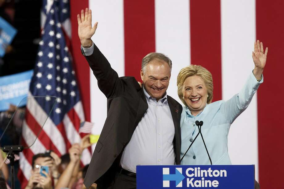 Hillary Clinton, presumptive 2016 Democratic presidential nominee, rightm and Tim Kaine, presumptive 2016 Democratic vice presidential nominee, wave during a campaign event in Miami, Florida, U.S., on Saturday, July 23, 2016.  Photo: Patrick T. Fallon, Bloomberg