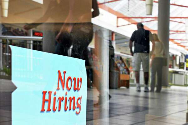 "A ""Now Hiring"" sign in a store window at Crossgates Mall in Guilderland.  (John Carl D'Annibale / Times Union)"