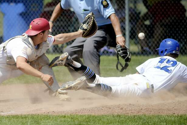 Bay City's Cheyne Maier, right, slides safe at home to score as Berryhill's Gabriel Denton loses the ball during the fifth inning on Saturday at Gladwin High School. Bay City won the district final game 7-2.