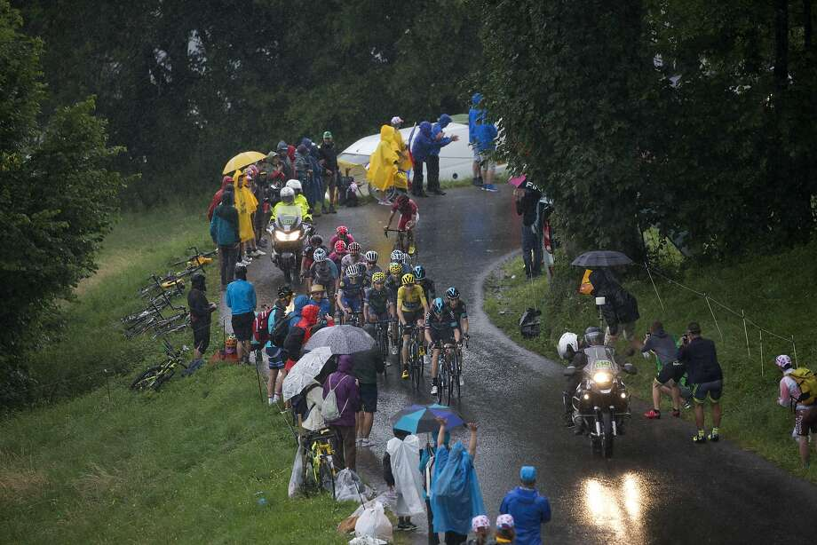 Chris Froome (yellow jersey) is well protected by his Sky teammates (in blue) on a rainy Saturday. Photo: Peter Dejong, Associated Press