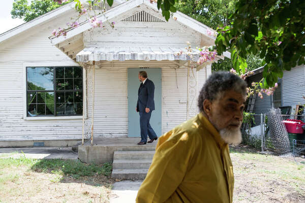 Attorney Jeff Mulliner looks at Nathaniel Word's home as Word stands in the front yard in San Antonio, Texas on July 1, 2016.  Word was acquitted in the murder of Anthony Coronado, an event which occurred in the front yard of Word's home.