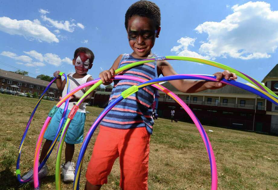 Juelz Pratt, 3, and Jaiden Sampson play with hula hoops at the Norwalk Community Health Center's second annual Community Health and Wellness Day on Saturday at Ryan Park in Norwalk. Photo: Erik Trautmann / Hearst Connecticut Media / Norwalk Hour