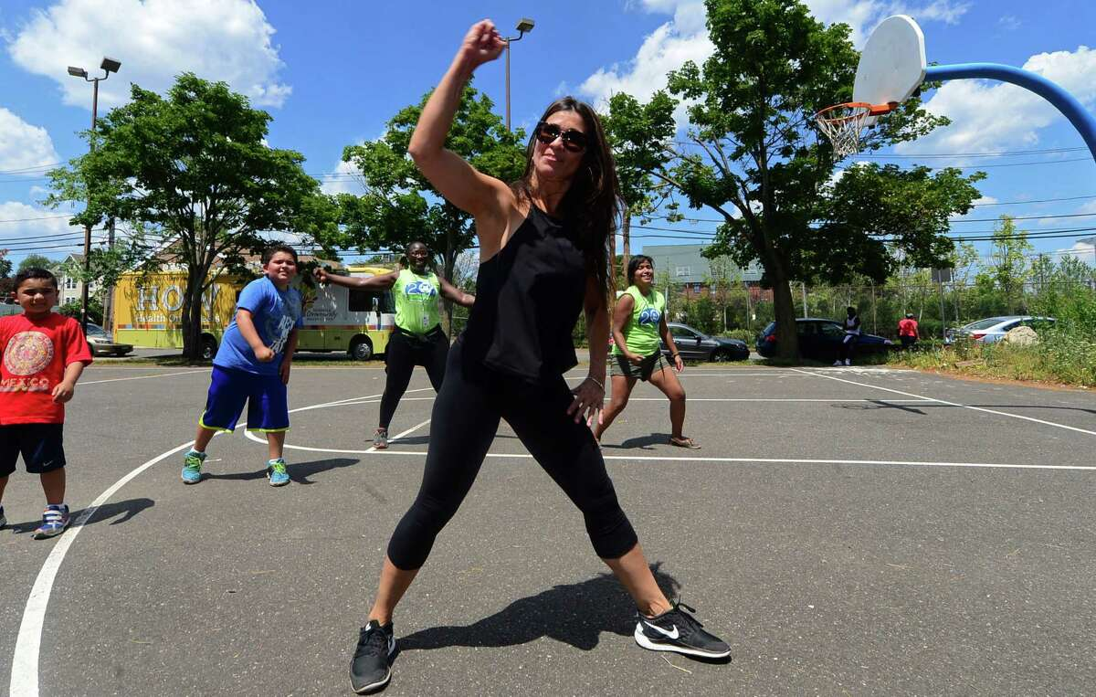 """Zumba instructor Edith Torres leads participants in a brief class as The Norwalk Community Health Center (NCHC) holds their 2nd annual Community Health & Wellness Day on Saturday, July 23, 2016, at Ryan Park in Norwalk, Conn. Each year, NCHC plans a day to give back to the community to provide a day of fun filled ?""""family?"""" activities at no cost. The event served hot dogs and hamburgers with basketball tournaments, face painting, bounce house, dance demonstrations as well as over 19 vendors who will promoted their services with tons of giveaways."""