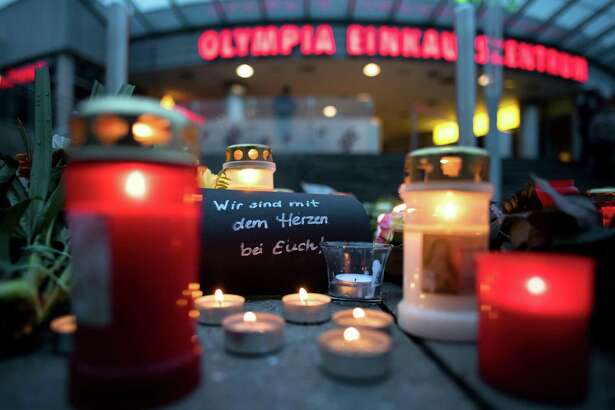 """Candles and a letter reading """"We are with you"""" lie in front of the Olympia-Einkaufszentrum shopping centre on July 23, 2016 in Munich, southern Germany, one day after a teenage German-Iranian gunman killed nine people and wounded 16. German police said there was an """"obvious"""" link between the actions of a teen gunman who killed nine people in a rampage in Munich, and those of Norwegian far-right mass murderer Anders Behring Breivik. / AFP PHOTO / dpa / Sven HoppeSVEN HOPPE/AFP/Getty Images ORG XMIT: 657108685"""