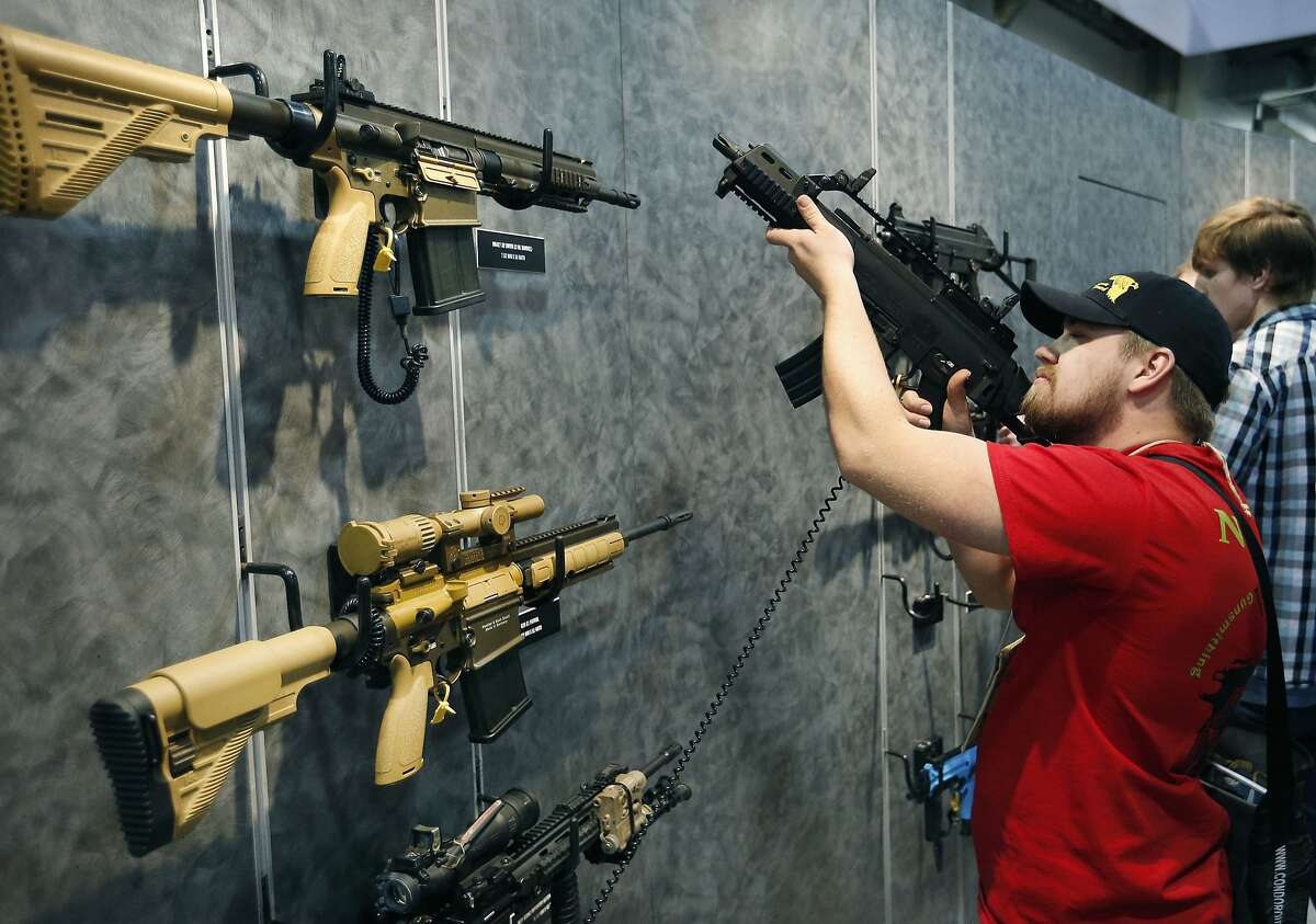 In this file photo, Nolan Hammer looks at a gun at the Heckler & Koch booth at the Shooting, Hunting and Outdoor Trade Show in Las Vegas.