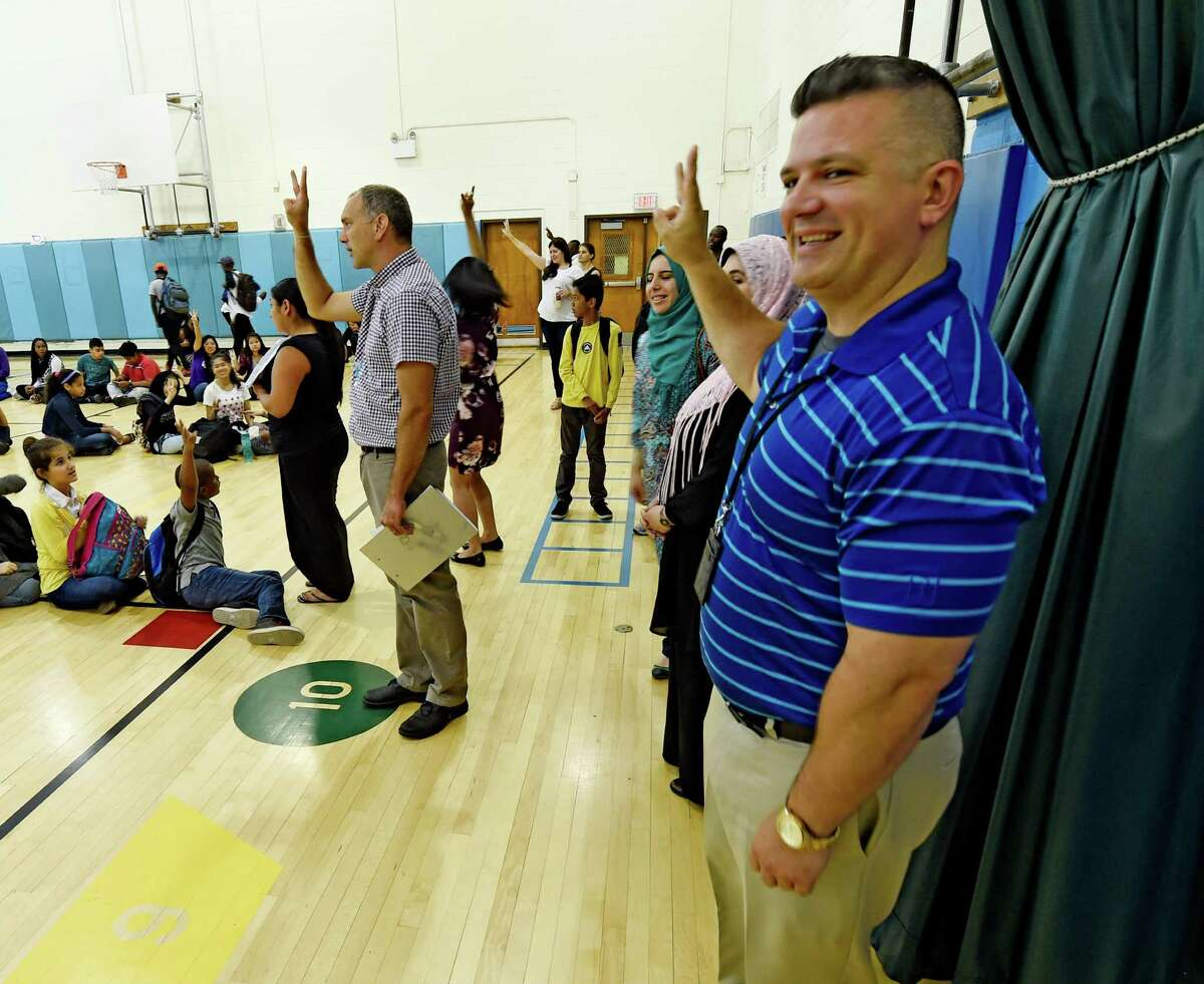 Tom Giglio, Director of english as new language as well as the Newcomer Program, right holds up the signal for quiet as classes are organized in the Newcomer Academy held at the Thomas O'Brien School Tuesday July 12, 2016 in Albany, N.Y. (Skip Dickstein/Times Union)
