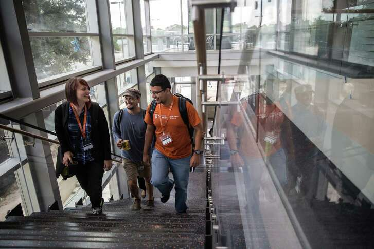 Amber Dunbar, David Woerner and Francisco Barrios, first-year medical students, walk up the grand staircase of the Health Learning Building, part of The University of Texas at Austin's new Dell Medical School on Wednesday, July 20, 2016. The Health Learning Building, which has over 2,000 panes of glass, is designed to feel welcoming and facilitate social interaction between students and faculty.