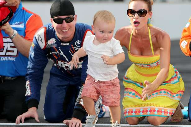 INDIANAPOLIS, IN - JULY 23:  Kyle Busch, driver of the #18 NOS Energy Drink Toyota, kisses the bricks with his wife, Samantha, and son, Brexton, after winning the NASCAR XFINITY Series Lilly Diabetes 250 at Indianapolis Motor Speedway on July 23, 2016 in Indianapolis, Indiana.  (Photo by Rey Del Rio/Getty Images)