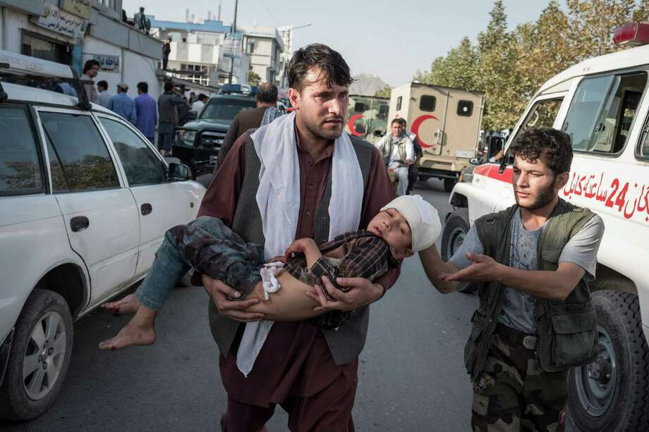 An injured child is evacuated after a suicide bombing targeted a demonstration by Hazaras, an ethnic minority group, in Kabul, Afghanistan, on Saturday. Photo: ADAM FERGUSON, STR / NYTNS