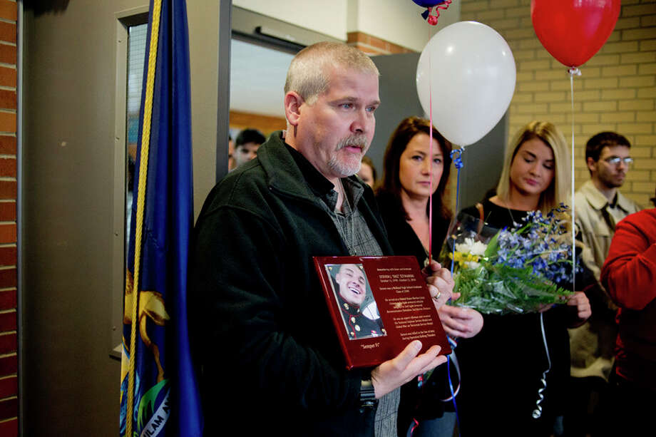John Szymanski talks about his son Steven Szymanski as he stands by his wife, Dawn, and daughter Ashlie, at Midland High School during a ceremony on Tuesday at Midland High School to honor the fallen Marine in this 2015 file photo. / Midland Daily News