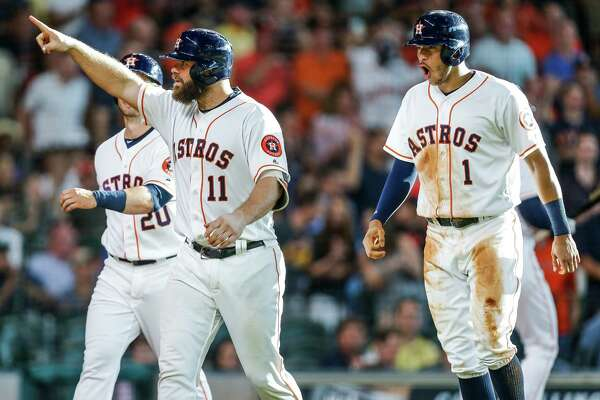Houston Astros catcher Evan Gattis (11) points to the crowd after hitting a home run to bring in Preston Tucker, left, and shortstop Carlos Correa (1), right, as the Houston Astros take on the Los Angeles Angels at Minute Maid Park Saturday, July 23, 2016 in Houston.