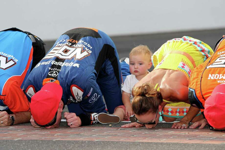 With son Brexton passing on a bit of tradition, Kyle Busch kisses the bricks along with his wife Samantha and crew members after winning Saturday's Xfinity Series race at Indianapolis Motor Speedway. Photo: Rey Del Rio, Stringer / 2016 Getty Images