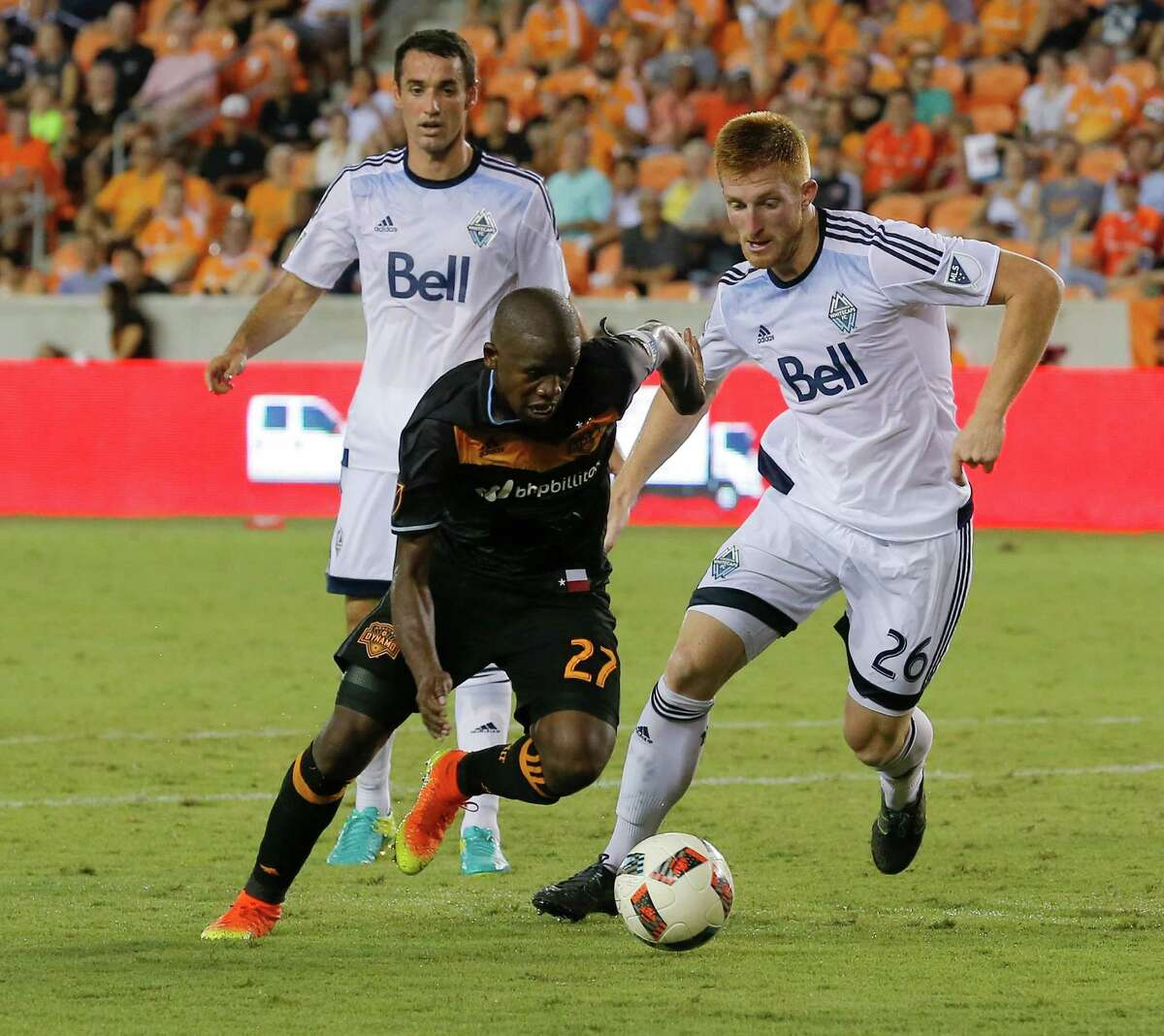 Houston Dynamo midfielder Oscar Garcia (27) dribbles around Vancouver Whitecaps defender Tim Parker (26) during the second half during an MLS soccer match Saturday, July 23, 2016, in Houston. Houston and Vancouver played to scoreless draw. (AP Photo/Bob Levey)