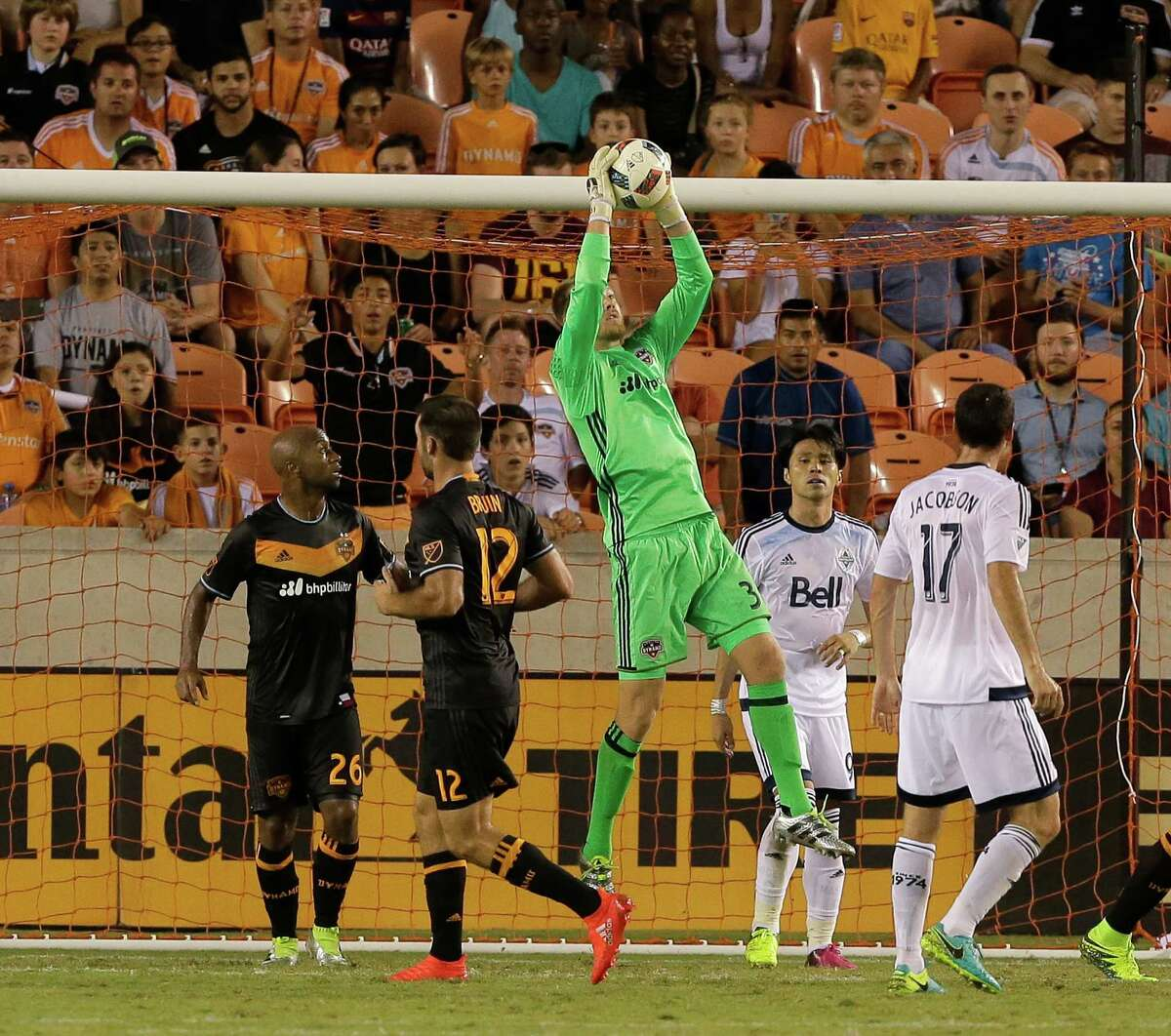 Houston Dynamo goalkeeper Joe Willis (31) makes save as Vancouver Whitecaps midfielder Andrew Jacobson (17) watches the second half during an MLS soccer match Saturday, July 23, 2016, in Houston. Houston and Vancouver played to scoreless draw. (AP Photo/Bob Levey)