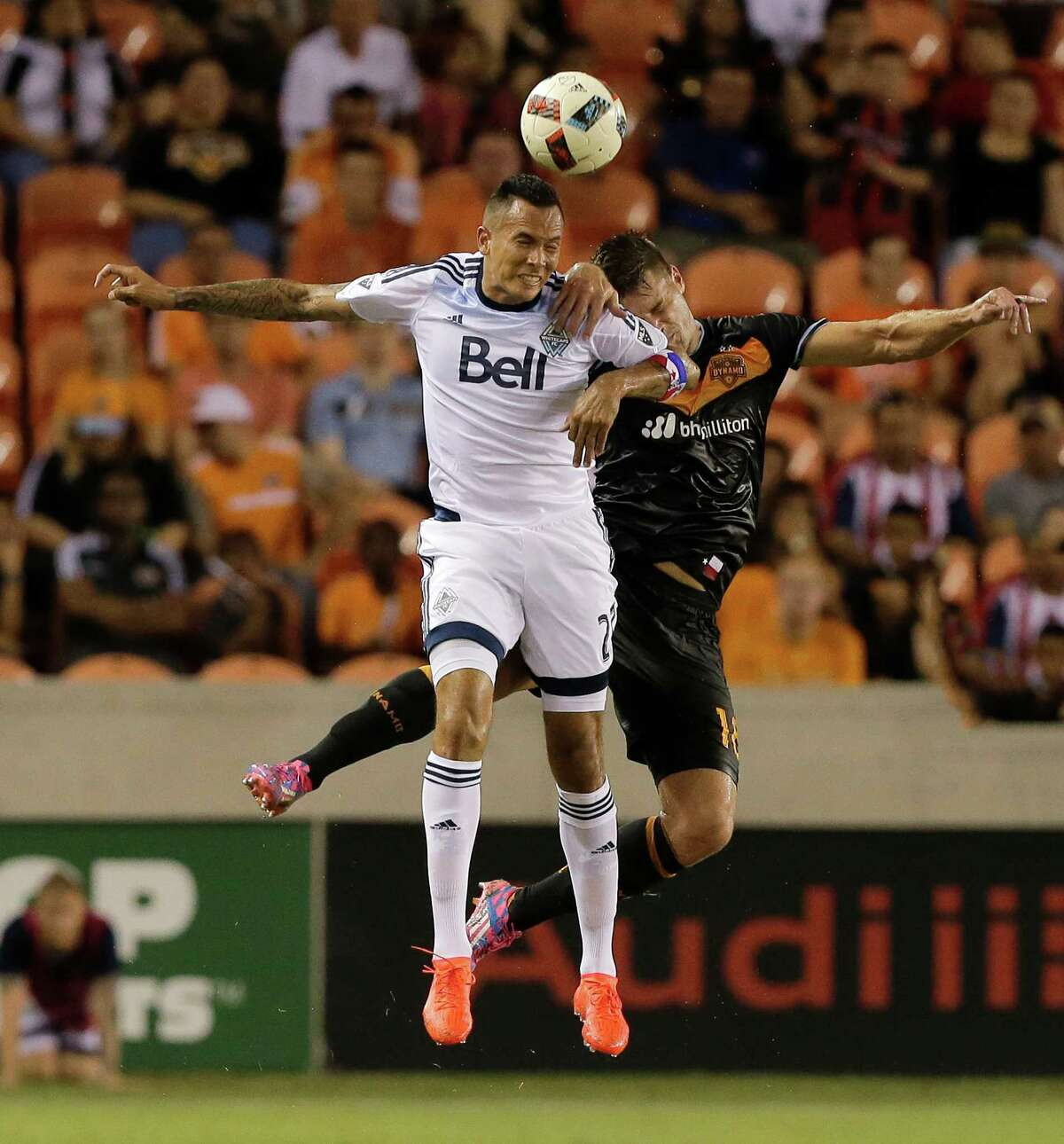 Vancouver Whitecaps forward Blas Perez (27) and Houston Dynamo defender David Horst (18) go up for a header during the second half during an MLS soccer match Saturday, July 23, 2016, in Houston. Houston and Vancouver played to scoreless draw. (AP Photo/Bob Levey)