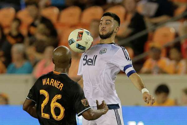 Vancouver Whitecaps midfielder Pedro Morales (77) chests the ball in front of Houston Dynamo midfielder Collen Warner (26) during the first half during an MLS soccer match Saturday, July 23, 2016, in Houston. (AP Photo/Bob Levey)