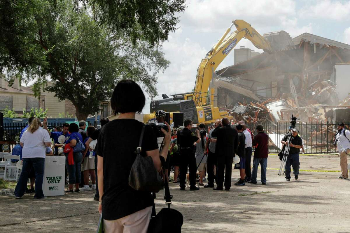 Members of the community gather to watch the demolition of the long-vacant Oakbrook Apartments near White Oak Bayou in northwest Houston on Saturday, July 23, 2016.