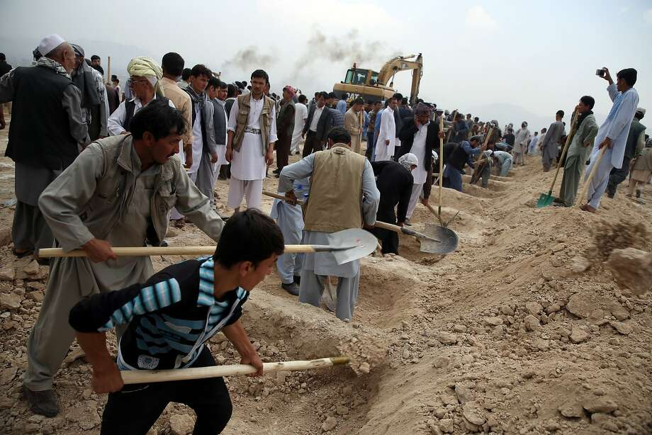 Afghans dig graves for victims of the suicide bombing in Kabul. The attack, claimed by the Islamic State group, killed at least 80 people who were taking part in a peaceful demonstration. Photo: Massoud Hossaini, Associated Press