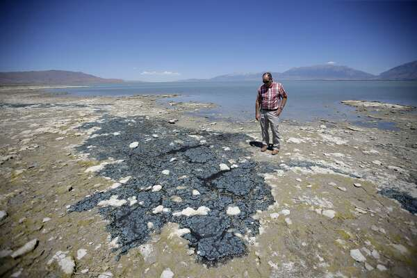 Bryce Larsen, environmental health director at the Utah County Health Department, looks at dried algae on the shore of Utah Lake Wednesday, July 20, 2016, near Spanish Fork, Utah. A huge toxic algal bloom in Utah has closed one of the largest freshwater lakes west of the Mississippi River, sickening more than 100 people and leaving farmers scrambling for clean water. The bacteria commonly known as blue-green algae has spread rapidly to cover almost all of 150-square-mile Utah Lake, turning the water a bright, anti-freeze green and leaving scummy foam along the shore. (AP Photo/Rick Bowmer)