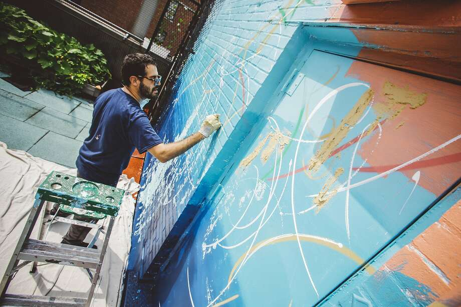 Artist Jose Parla paints a mural at the Incarnation Children's Center in New York City. Parla also decorated bedrooms at the center, which specializes in treating HIV-positive children. Photo: Duffy Higgins, Associated Press