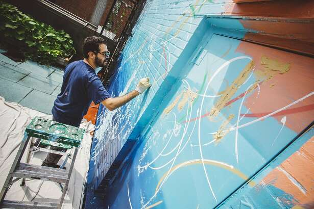 In this July 20, 2016, photo provided by Kiehl's, artist Jose Parla paints a mural at the Incarnation Children's Center in New York. Parla spent several days at the facility that specializes in treating HIV-positive children, decorating bedrooms, hallways and common areas of the residence in his signature improvisational style, the latest project in a charitable effort that commissions top contemporary artists to make pediatric health facilities less intimidating. (Duffy Higgins/Courtesy of Kiehl's via AP)
