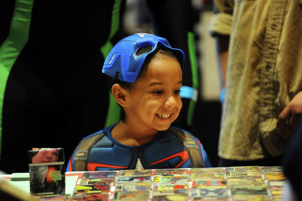 Five-year old Tommy Ligon Jr., dressed as Captain America, smiles while looking at old comic books during the first ever Lock City Comic Con held at the Italian Center of Stamford, on Newfield Avenue, on Sunday, July 24, 2016.