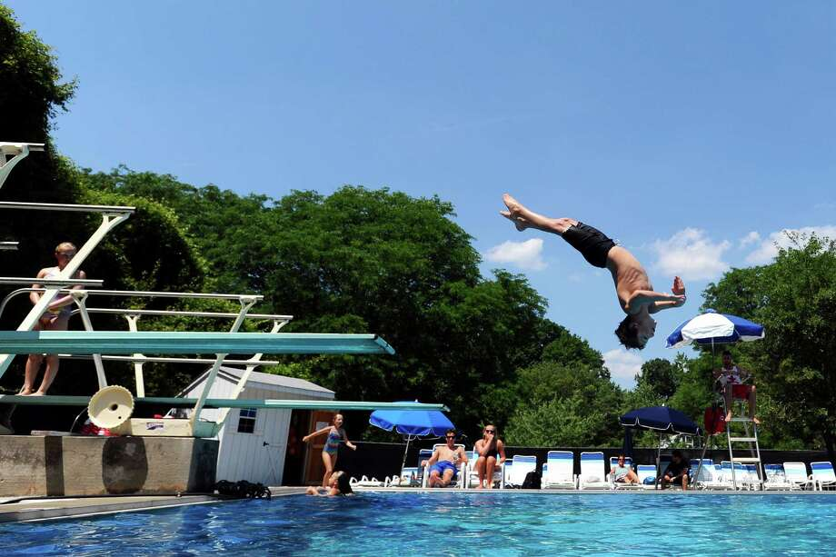 Quinn Neyer, 7, dives backwards into the pool during a diving class at the Newfield Swim and Tennis Club on Thursday. Photo: Michael Cummo / Hearst Connecticut Media / Stamford Advocate