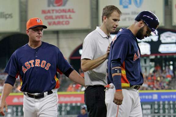 Houston Astros manager A.J. Hinch checks on Marwin Gonzalez as he is being assisted by head trainer Jeremiah Randall after getting hurt running to first base during the fifth inning against the Los Angeles Angels at Minute Maid Park Sunday, July 24, 2016, in Houston. Danny Worth was put in as a pinch runner.