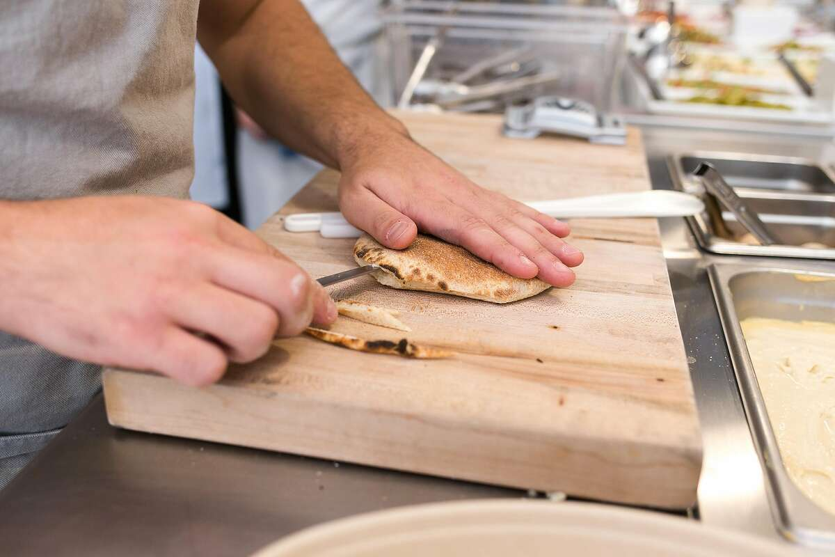 Guy Eshel cuts open bread for a pita sandwhich at Sababa in S.F.