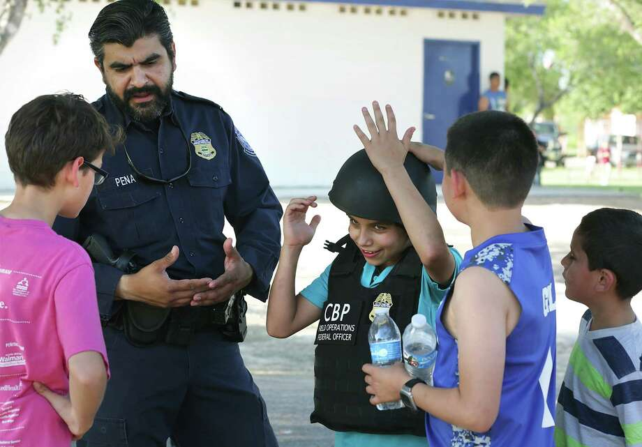 CBP Agent Arturo Pena, left, helps Diego Segovia, center and Gil Gil, right, as they try on protective gear. The U.S. Customs and Border Protection band knows as Los Federales, played at a CBP community outreach event at Bonita Park near Rio Grande City, on Wednesday, May 4, 2016. Photo: Bob Owen, Staff / San Antonio Express-News / ©2016 San Antonio Express-News