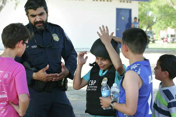 CBP Agent Arturo Pena, left, helps Diego Segovia, center and Gil Gil, right, as they try on protective gear. The U.S. Customs and Border Protection band knows as Los Federales, played at a CBP community outreach event at Bonita Park near Rio Grande City, on Wednesday, May 4, 2016.
