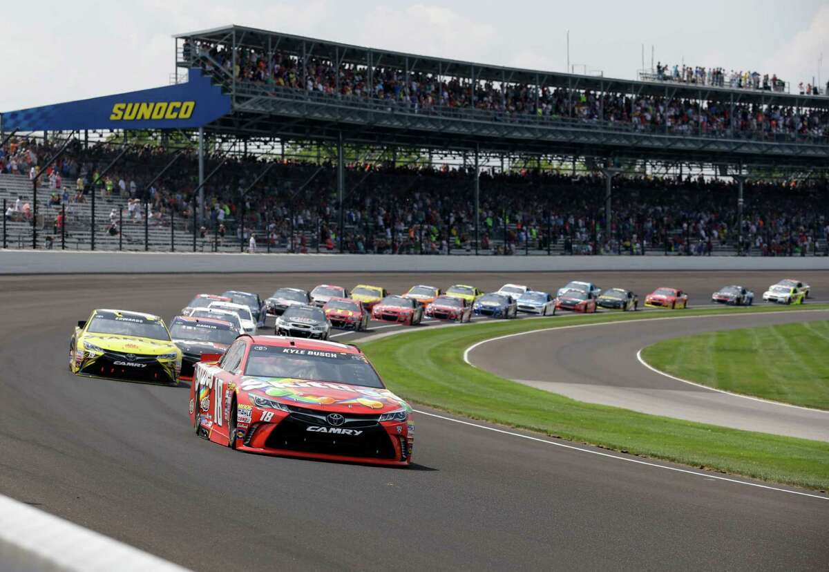 Kyle Busch (leads the field through the first turn on the start of the Brickyard 400 NASCAR auto race at Indianapolis Motor Speedway in Indianapolis, Sunday, July 24, 2016.