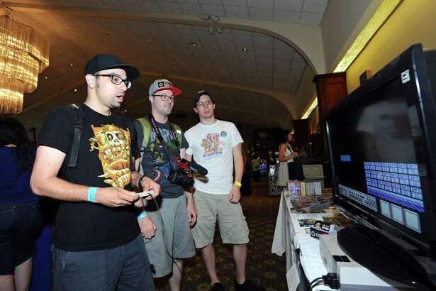 David Apuzzo, left, plays Super Mario on a Ninetendo with friend Russell Lyman (center) and Gregory Draudt of Gorilla Games looking on during the first ever Lock City Comic Con held at the Italian Center of Stamford, on Newfield Avenue, on Sunday, July 24, 2016.