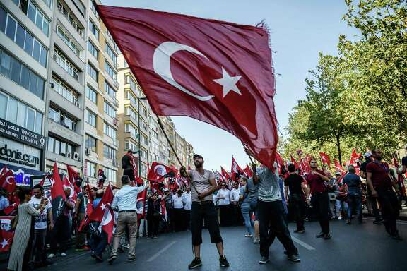 A demonstrator waves a Turkish flag Sunday near Istanbul's Taksim Square during the first cross-party rally to condemn the coup attempt against President Recep Tayyip Erdogan.