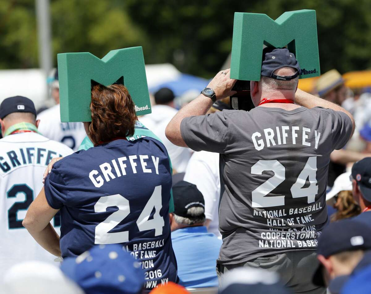 Fans of inductee Ken Griffey Jr. stand at the start of the National Baseball Hall of Fame induction ceremony at Clark Sports Center on Sunday, July 24, 2016, in Cooperstown, N.Y. (AP Photo/Mike Groll)