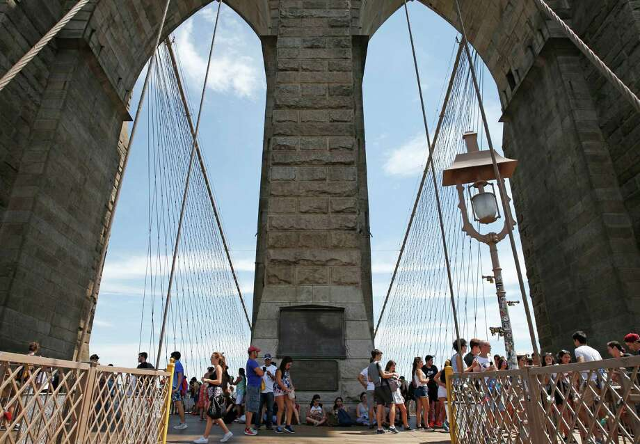 Tourists cluster in the shadow of one of the towers of the Brooklyn Bridge, Sunday, July 24, 2016, in New York, as excessive heat continued to blanket the Northeast. Temperatures continued into the 90's for the fourth consecutive day with no relief in sight for the next several days. (AP Photo/Kathy Willens) Photo: Kathy Willens, STF / Copyright 2016 The Associated Press. All rights reserved. This material may not be published, broadcast, rewritten or redistribu