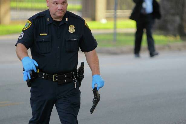 A police officer carries a pellet gun at the site of an officer-involved shooting Sunday. The man who was shot was taken to Ben Taub General Hospital.