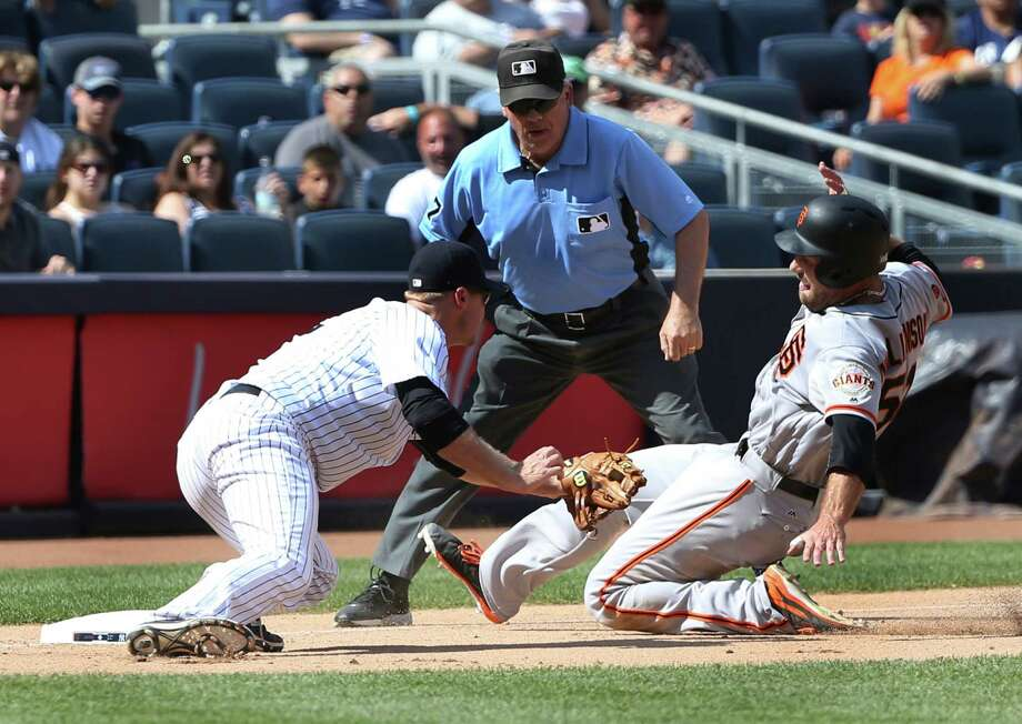 New York Yankees third baseman Chase Headley, left, completes a double play by tagging out San Francisco Giants' Mac Williamson at third base during the eighth inning of the baseball game at Yankee Stadium, Sunday, July 24, 2016 in New York. (AP Photo/Seth Wenig) ORG XMIT: NYSW114 Photo: Seth Wenig / Copyright 2016 The Associated Press. All rights reserved. This m