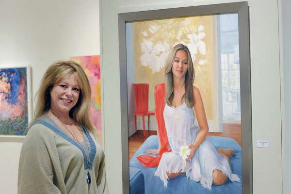 """Jeanine C. Jackson, president of the Connecticut Society of Portrait Artists, next to her oil painting titled """"Nora"""" in the Flinn Gallery at Greenwich Library on Thursday. Jackson said the work is a tribute to motherhood."""