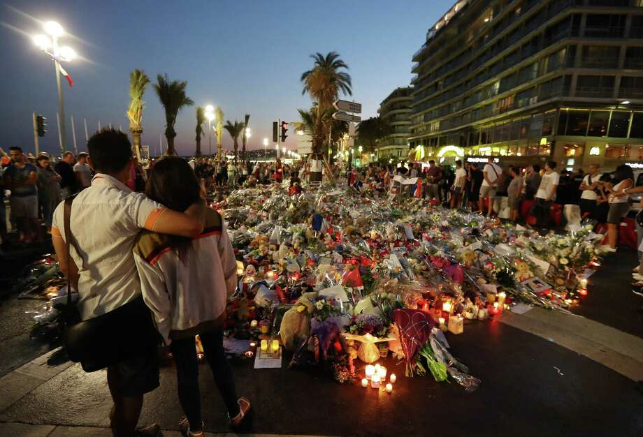 People stand in front of flowers, candles and messages laid at a makeshift memorial in Nice on July 18, 2016, in tribute to the victims of the deadly attack on the Promenade des Anglais seafront which killed 84 people. France was set to hold a minute's silence on July 18, 2016 to honour the 84 victims of Mohamed Lahouaiej-Bouhlel, a 31-year-old Tunisian who drove a truck into a crowd watching a fireworks display on Bastille Day, but a period of national mourning was overshadowed by bickering politicians. Church bells will toll across the country, and the country will fall silent at midday, a now grimly familiar ritual after the third major terror attack in 18 months on French soil. / AFP PHOTO / Valery HACHEVALERY HACHE/AFP/Getty Images Photo: VALERY HACHE, Staff / AFP or licensors