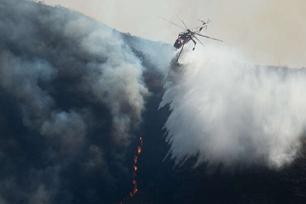 A helicopter drops water on the Soberanes Fire in Carmel Highlands, California on July 23, 2016. The fire has burned more than 14,000 acres and threatens 1,650 structures, according to Cal Fire.