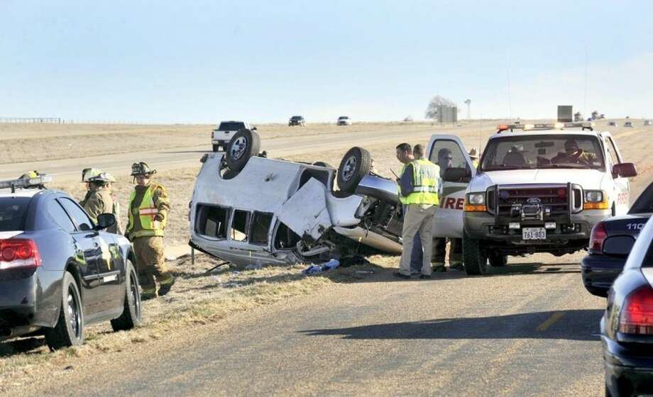 Emergency personnel investigate a single-vehicle accident that left three victims dead Friday on Interstate 27 two miles south of Canyon. The van was carrying 15 workers on their way to work at Cargill in Plainview. Photo: Michael Schumacher/Amarillo Globe-News