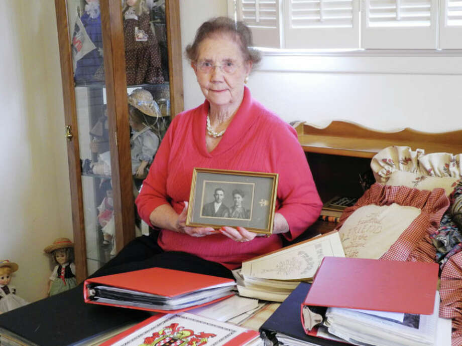 Surrounded by her research, June Wells holds up a photograph of her parents. Photo: Gail M. Williams | Plainview Herald