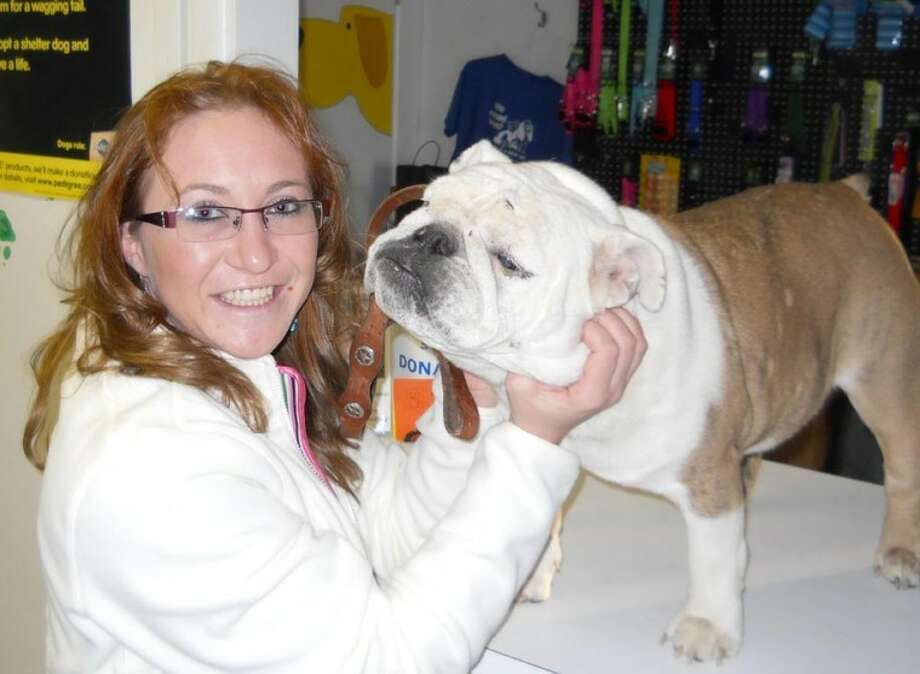 Georgia Berry of Canyon was reunited last week with Ollie after the English bulldog disappeared from her Amarillo apartment 26 months earlier. Berry isn't sure how the dog got to Plainview, where it had been living with a family the past two years before animal control officer Rey Mora tracked down its real owner. Photo: Courtesy Photo By Rey Mora
