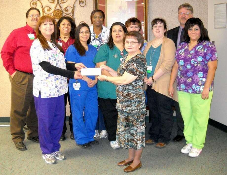 "Faith In Sharing House representative Janis Miller (front right) accepts a $333.33 check from Estella Martinez and other members of team Roly-Poly at Covenant Hospital Plainview. As part of efforts to improve the health and wellbeing of employees and also help someone in need, Covenant Health System conducted the ""Give From The Gut"" weight loss challenge. The team that had the highest percentage of weight loss won award points for each member of the team and $1,000 for the charity of their choice. Team Roly-Poly finished in a three-way tie for first and opted to donate their share of the winnings to FISH. Others shown are (back, from left) Mark Martinez, Dee Zapata, Danielle McDonald, Susan Harman and CHP CEO Alan King; (front) Martinez, Sandra Almador, Patricia Reyes, Miller, Renee Branch and Charlene Hilerio."