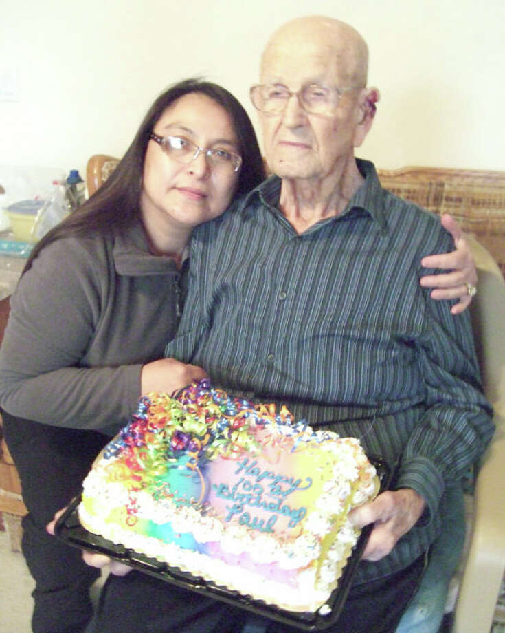 Long-time caregiver Bella Trujillo hugs Paul Lindsey and gives him a cake Monday on the occasion of his 100th birthday. Photo: Shanna Sissom/Plainview Herald